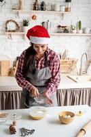 jovem latina servindo farinha na massa e cozinhando na cozinha foto