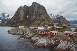 casas vermelhas de pescadores à beira-mar e montanhas foto