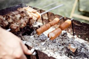 close up de kebabs em espetos, homem grelhando carne ao ar livre foto