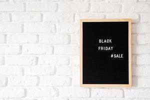 venda de texto preto sexta-feira no quadro de letras preto na parede de tijolos brancos foto