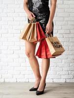 pernas de mulher com sacolas de compras, texto preto sexta-feira em sacola de papel foto
