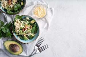 vista superior de tigelas de salada de abacate e espinafre fresco no verão foto