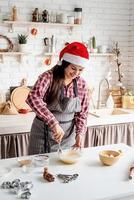 jovem latina misturando massa para cozinhar na cozinha foto