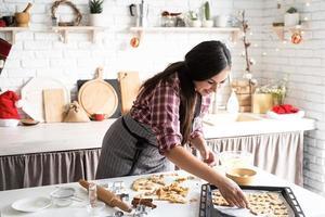 jovem morena fazendo biscoitos na cozinha foto
