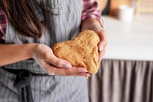 mulher com as mãos segurando uma massa em forma de coração foto