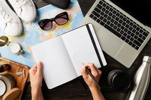 vista de cima mulher planejando uma viagem, escrevendo em um caderno foto