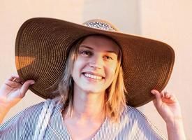 mulher alegre com roupas de verão segurando o chapéu olhando para a câmera foto