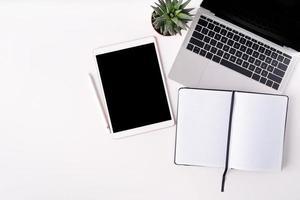 mesa branca moderna com laptop, tablet e caderno em branco foto