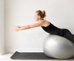 jovem mulher desportiva sentada sobre a bola de fitness foto