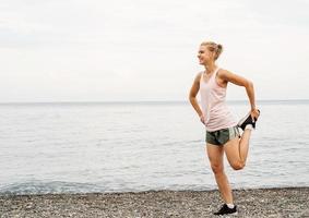 mulher atleta blong fazendo exercícios de alongamento na praia foto