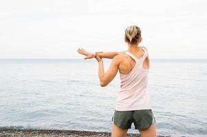 mulher atleta blong fazendo exercícios na praia foto