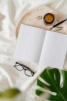 livro aberto, óculos, vela e flores vista de cima na cama branca foto