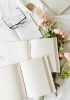 livros abertos e flores vista superior na cama branca. mock up design foto