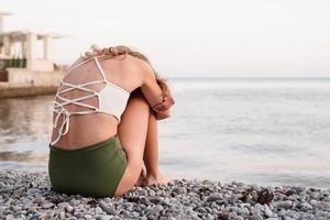 jovem mulher deprimida sentada na praia, vista traseira foto