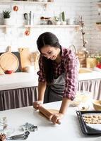 mulher com as mãos amassando massa na cozinha foto