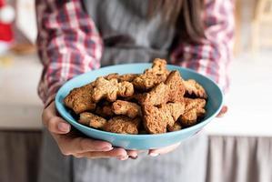 Mulher com as mãos segurando um prato com biscoitos caseiros na cozinha foto