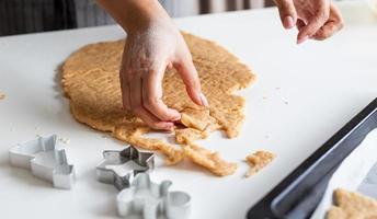 mulher com as mãos assando biscoitos na cozinha foto