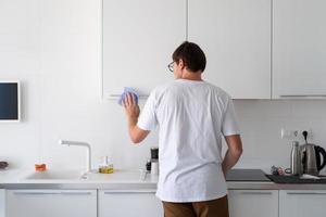 homem limpando as superfícies da cozinha foto