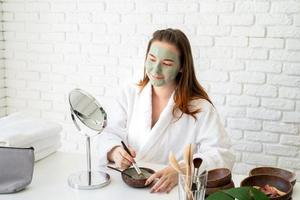 mulher usando roupão de banho aplicando máscara facial de argila olhando para o espelho foto