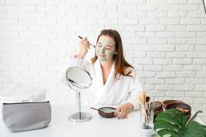 mulher vestindo roupão de banho aplicando máscara facial de argila, olhando para o espelho foto