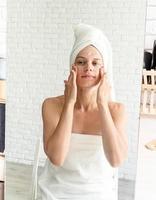mulher fazendo maquiagem matinal, aplicando creme no rosto, olhando no espelho foto