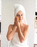 mulher com toalhas de banho brancas fazendo maquiagem matinal olhando para o espelho foto
