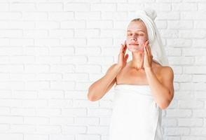 jovem com toalhas de banho brancas aplicando esfoliante no rosto e pescoço foto