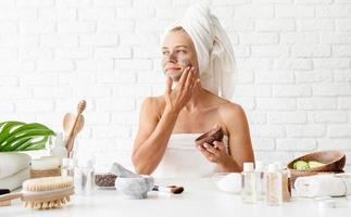 mulher usando toalhas brancas aplicando máscara facial de argila do spa no rosto foto