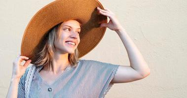 mulher na rua segurando o chapéu olhando o pôr do sol foto