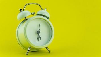 despertador branco sobre fundo amarelo mesa. foto