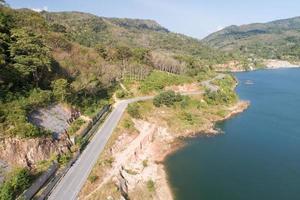 vista aérea da estrada ao redor da paisagem de árvores da floresta do lago da represa. foto