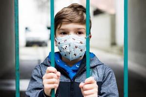 garoto com máscara facial em pé atrás do portão durante o bloqueio covid-19. foto