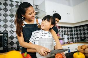 família feliz ajuda a cozinhar a refeição juntos na cozinha em casa. foto