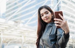 mulheres bonitas asiáticas jovens usando smartphone tirem uma selfie. foto