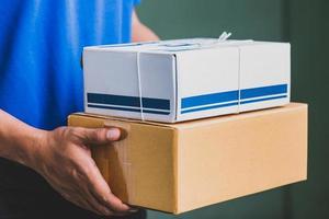 feche o entregador em uniformes azuis, segurando a caixa de papelão do pacote. foto