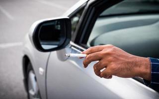 jovem fumando um cigarro no carro. foto