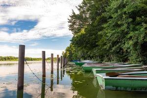 barcos a remo ficam na margem de um lago na bavária com uma floresta foto