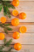 moldura feita de galhos de pinheiro e tangerinas em fundo de madeira. foto