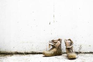 bota militar velha no fundo da parede branca foto
