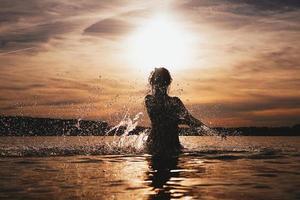 jovem modelo nadando no mar - hora do pôr do sol foto