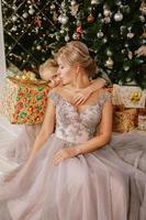 filha abraçando a mãe enquanto está sentada na árvore de natal foto