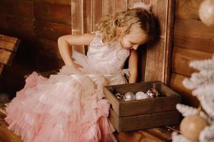 linda garota em um vestido rosa elegante olhando para uma caixa de madeira com bolas foto