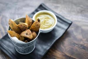 fatias de batata frita com salgadinhos de molho de curry foto