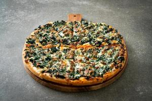 Pizza de espinafre e queijo na bandeja de madeira foto