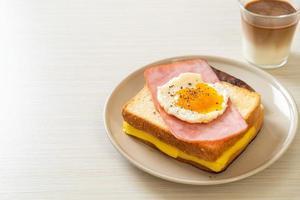 pão torrado queijo com cobertura de presunto e ovo frito com linguiça de porco foto