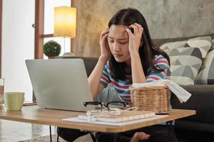 mulher asiática que trabalha em casa está estressada e dor de cabeça. foto