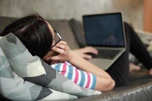 mulher asiática, trabalhando em casa, deitada e usando um telefone celular. foto