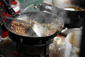 cozinhando carne de porco picada tailandesa refogada com manjericão na frigideira de metal foto