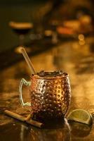 Coquetel tropical com rum picante, canela e limão, em bar foto