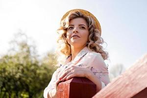 linda mulher com vestido de verão e chapéu de palha foto